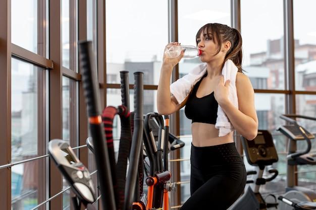 Bocznego widoku kobieta przy gym nawadniać