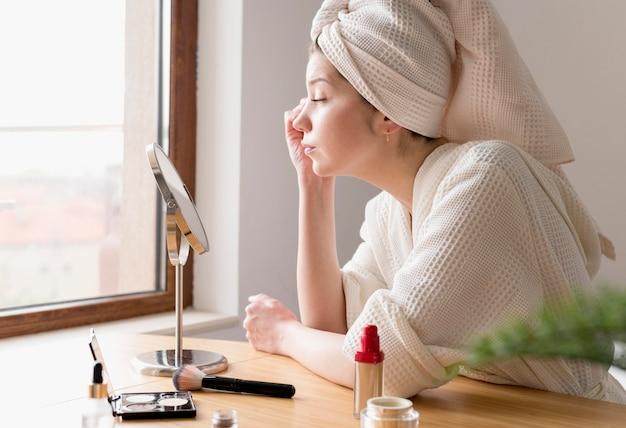 Bocznego widoku kobieta stosuje eyeliner