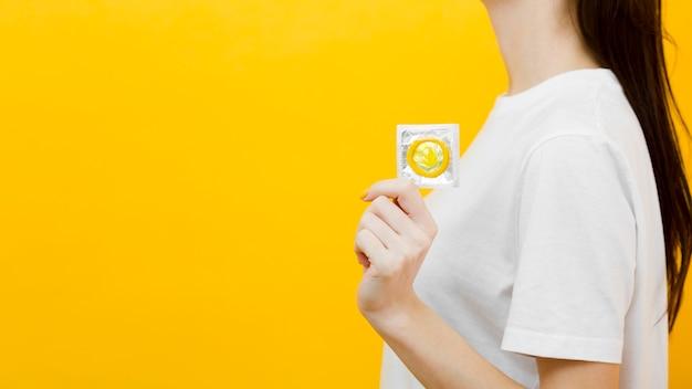 Bocznego widoku kobieta trzyma kondom z kopii przestrzenią