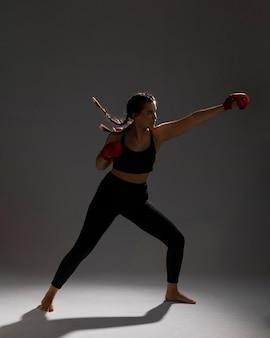 Bocznego widoku kobieta uderza pięścią z pudełkowatymi rękawiczkami