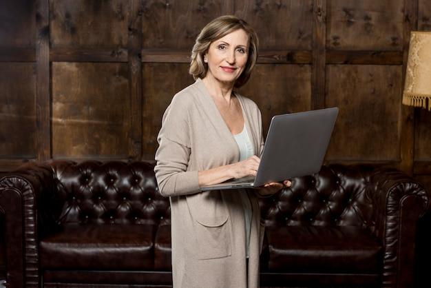 Bocznego widoku kobieta używa laptop
