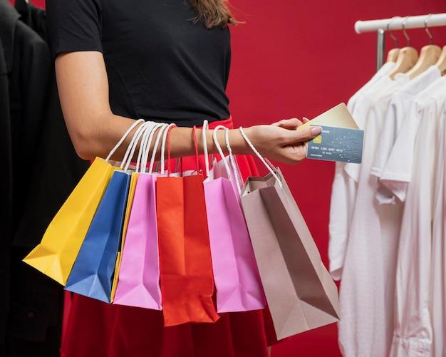 Bocznego widoku kobieta z kolorowymi torbami przy zakupy
