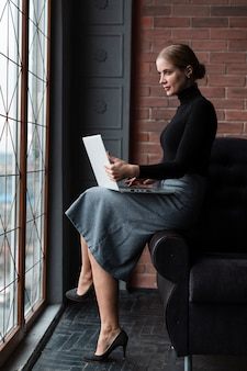 Bocznego widoku kobieta z laptopem