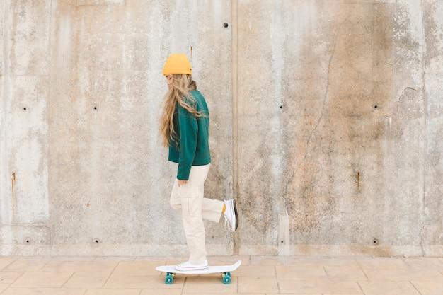 Bocznego widoku kobieta z łyżwowy plenerowym