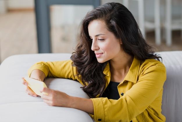 Bocznego widoku kobieta z smartphone na kanapie