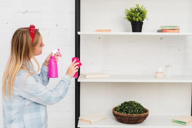 Bocznego widoku kobiety cleaning półki