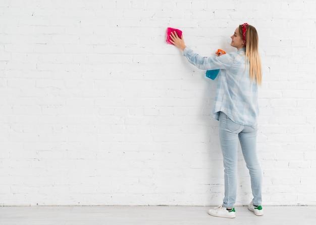 Bocznego widoku kobiety cleaning ściana