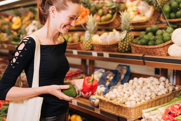 Bocznego widoku kobiety mienia avocado i dzwonkowy pieprz