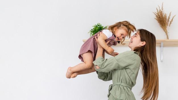 Bocznego widoku kobiety mienia dzieciak