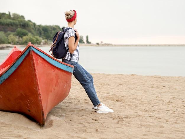 Bocznego widoku kobiety obsiadanie na łodzi