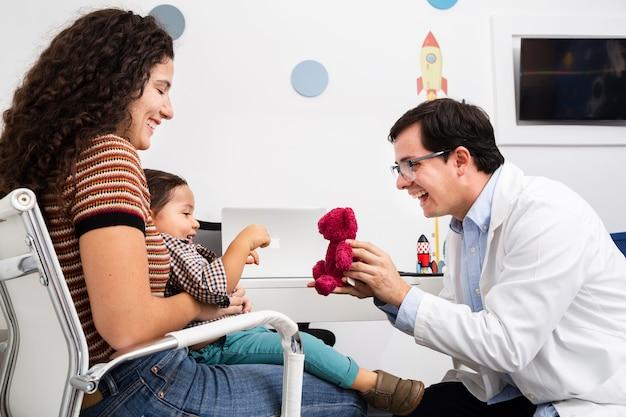Bocznego widoku lekarka bawić się z chłopiec