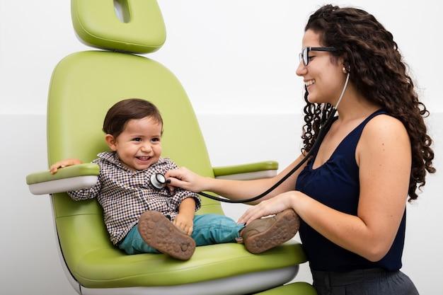 Bocznego widoku lekarka egzamininuje dzieciaka