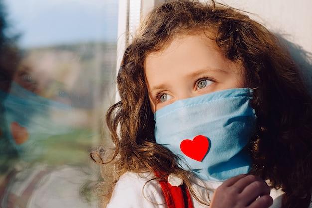Bocznego widoku mała dziewczynka jest ubranym ochronną twarz maskę z czerwonym sercem, siedzi na parapecie w domu, patrzejący na zewnątrz zamazanego okno. pozostań w domu zapobieganie pandemii koronawirusa kwarantanny. kwarantanna domowa