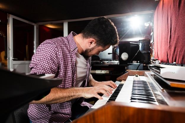 Bocznego widoku mężczyzna bawić się klawiaturę w studiu
