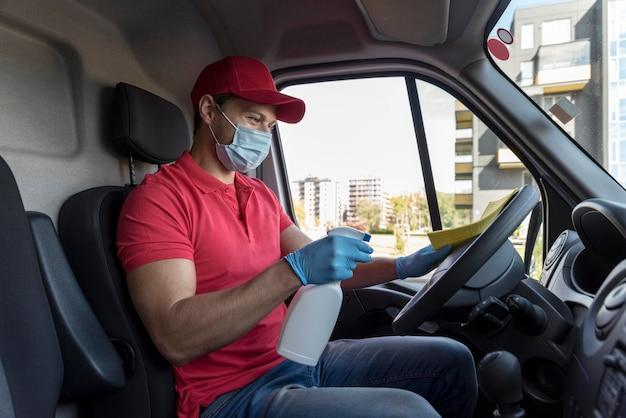 Bocznego widoku mężczyzna czyści samochód