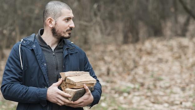 Bocznego widoku mężczyzna niesie drewno