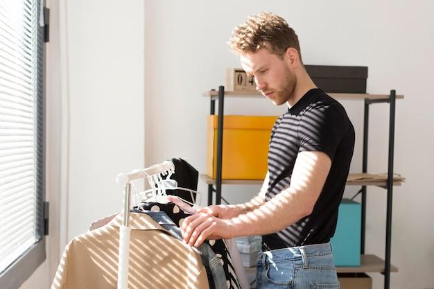 Bocznego widoku mężczyzna patrzeje ubrania
