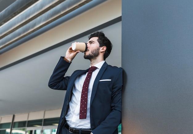 Bocznego widoku mężczyzna pije kawę w kostiumu