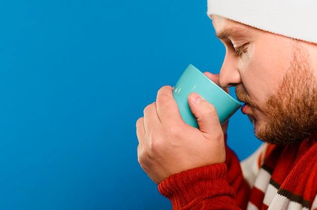 Bocznego widoku mężczyzna pije niektóre herbaty