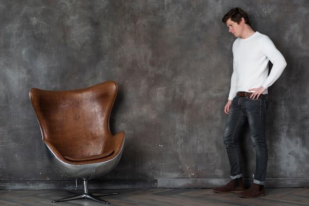 Bocznego widoku mężczyzna pozuje obok rzemiennego krzesła