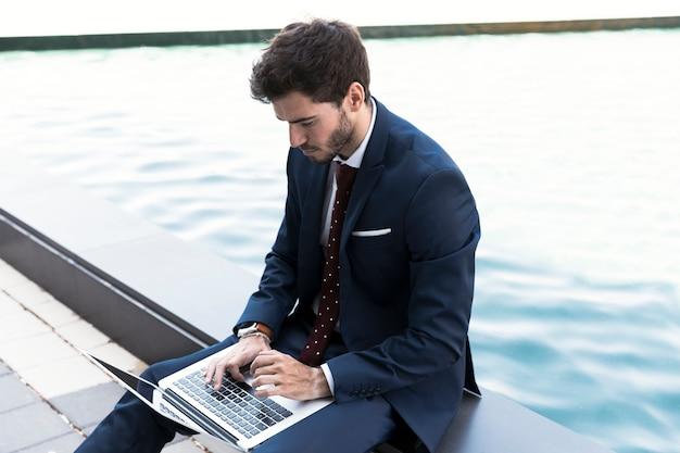Bocznego widoku mężczyzna pracuje na jego laptopie