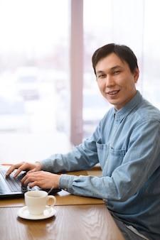 Bocznego widoku mężczyzna pracuje na laptopie