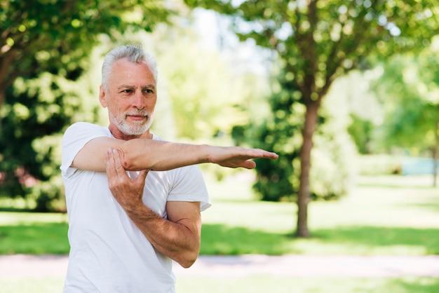 Bocznego widoku mężczyzna rozciąga jego rękę