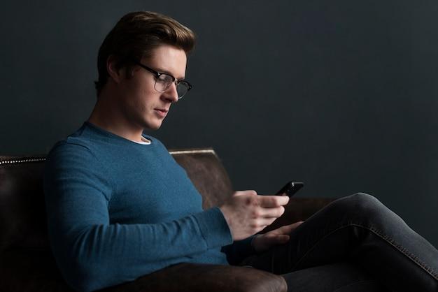 Bocznego widoku mężczyzna sprawdza ogólnospołeczne środki na telefonie
