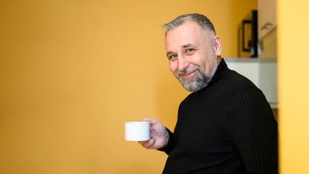 Bocznego widoku mężczyzna trzyma filiżankę herbata
