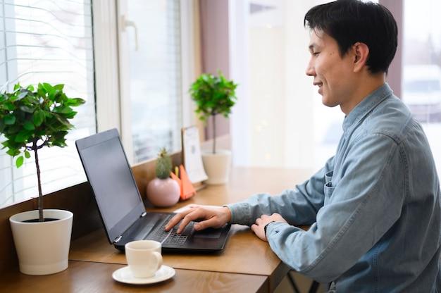 Bocznego widoku mężczyzna używa laptop