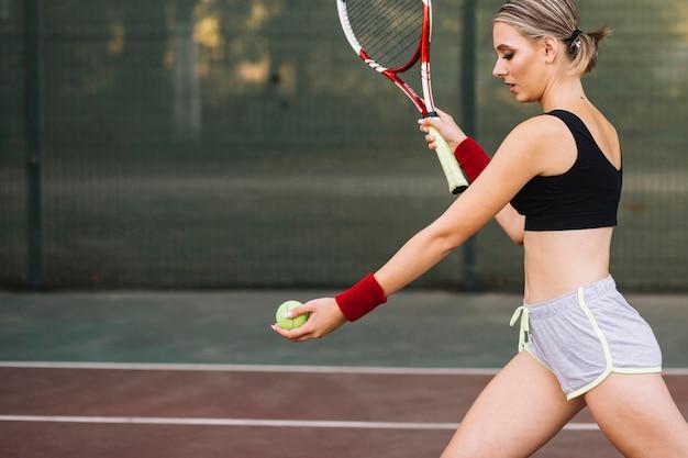 Bocznego widoku młoda kobieta przygotowywająca słuzyć tenisową piłkę