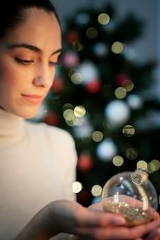 Bocznego widoku młoda kobieta trzyma boże narodzenie kulę ziemską