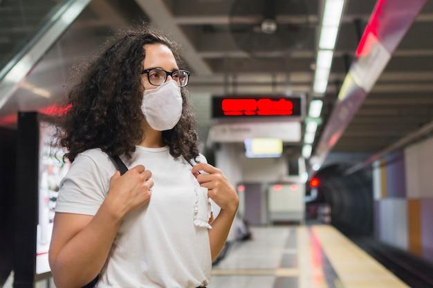 Bocznego widoku młoda kobieta z medycznym maskowym czekaniem dla metra