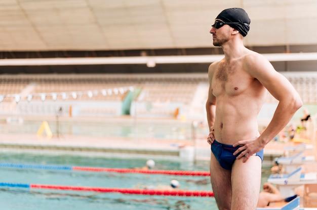 Bocznego widoku młoda samiec przy pływackim basenem