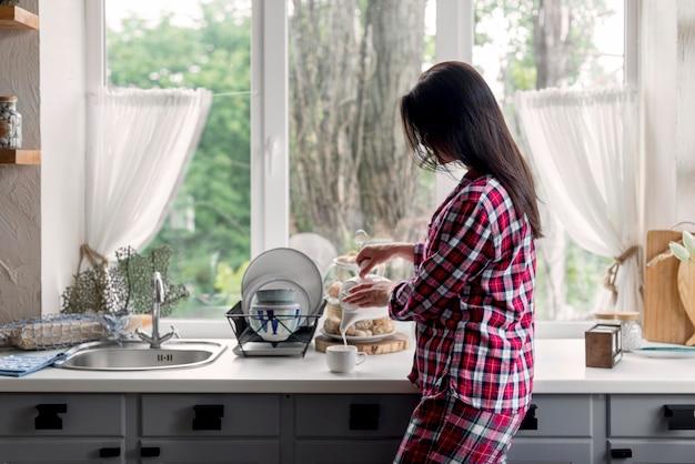 Bocznego widoku młodej kobiety narządzania herbata