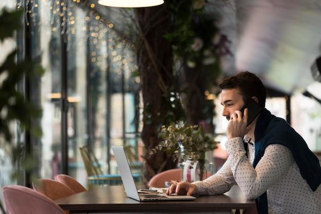 Bocznego widoku młody biznesowy mężczyzna opowiada nad telefonem