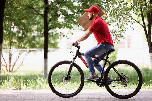 Bocznego widoku młody człowiek dostarcza pakuneczek na rowerze