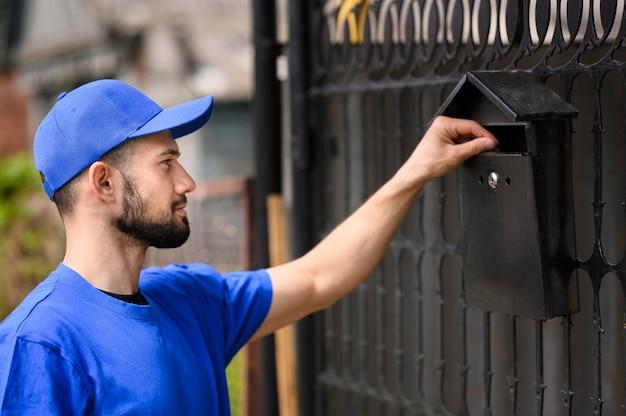 Bocznego widoku młody człowiek dostarcza poczta