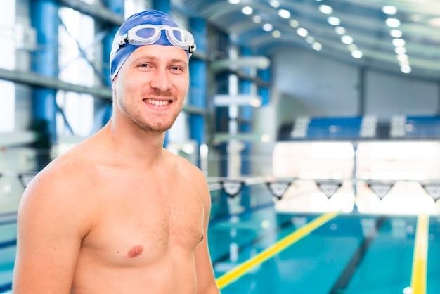 Bocznego widoku młody człowiek z gogle przy basenem