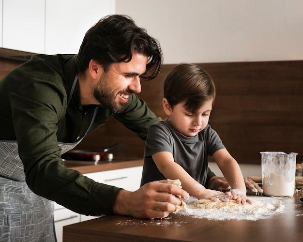 Bocznego widoku ojciec i syn robi ciastu