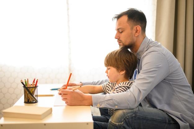 Bocznego widoku ojciec i syn z ołówkami