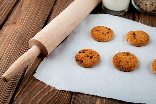 Bocznego widoku owsiani ciastka na kalkowanie papierze i tocznej szpilce na drewnianym tle