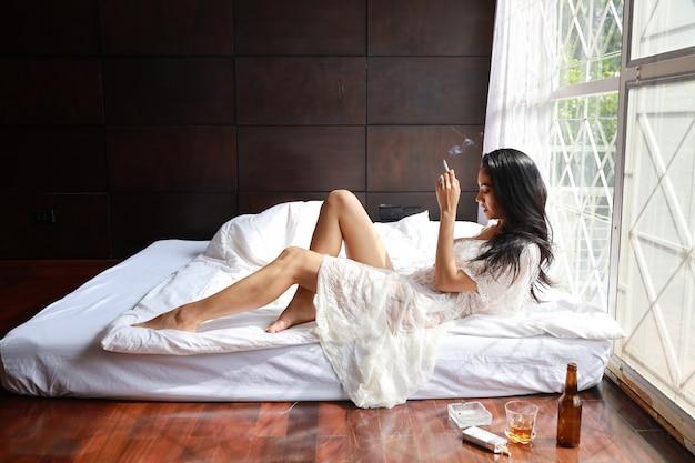 Bocznego widoku pijana azjatykcia kobieta w białej bieliźnie pije i dymi, podczas gdy trzymający butelkę trunku alkohol i kłamający na łóżku w sypialni