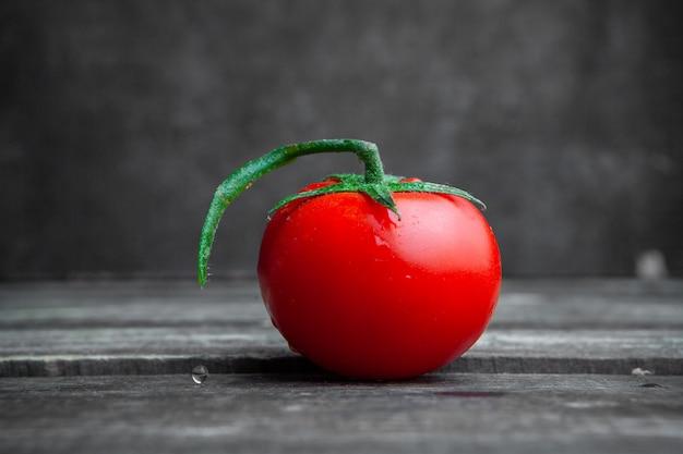 Bocznego widoku pomidor na ciemnym drewnianym i textured tle. poziomy