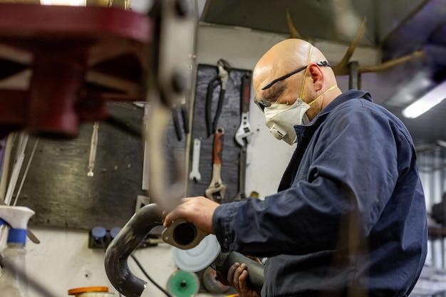 Bocznego widoku portret pracuje w garażu naprawia motocykl i dostosowywa mężczyzna