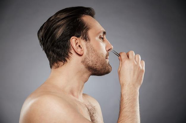 Bocznego widoku portret przystojny mężczyzna usuwa włosy w nosie