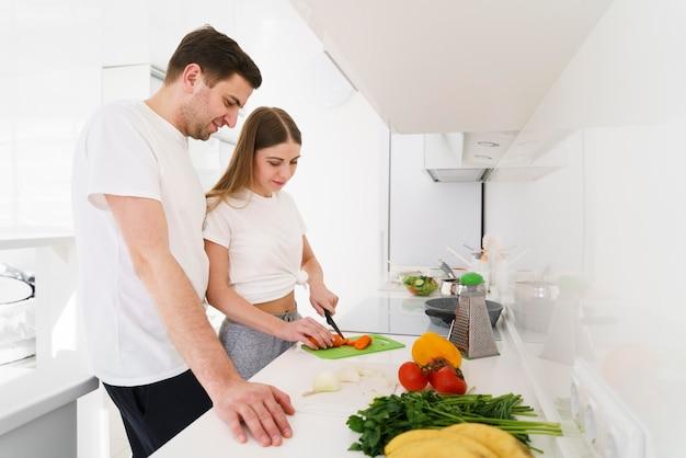 Bocznego widoku potomstw para w kuchni