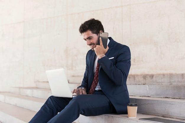 Bocznego widoku prawnik opowiada na telefonie z laptopem