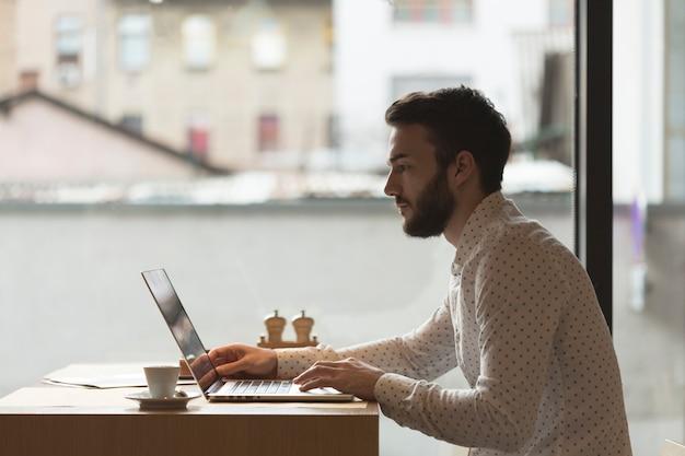 Bocznego widoku przedsiębiorca pracuje na laptopie