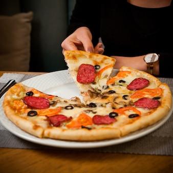 Bocznego widoku przyrodnia kiełbasiana pizza z istotą ludzką w bielu talerzu